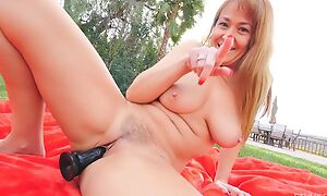 Horn-mad GILF with natural boobs fucks herself outdoors